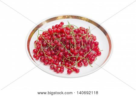 Berries of fresh redcurrant on a saucer on a light background