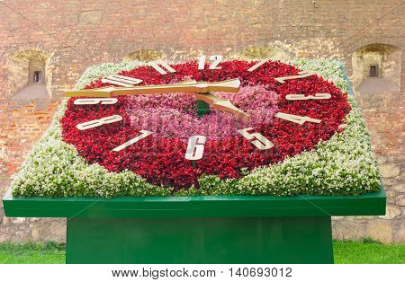 Flower clock with clock face made of white red and pink flowers on a background of old brick fortress wall