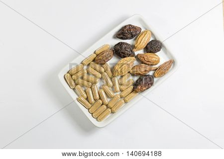 Herb with capsule and thai herb on white dish