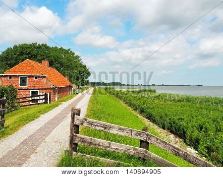Old Farmhouse out of red Bricks behind an old Sea-Dyke