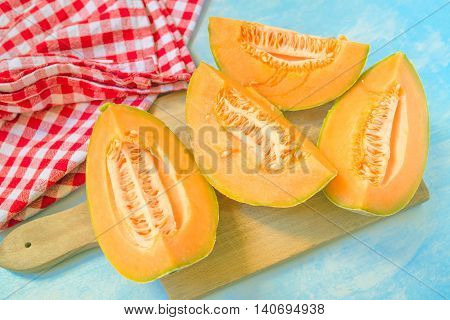 Four slices of cantaloupe melon on rustic table tasty summer refreshment selective focus