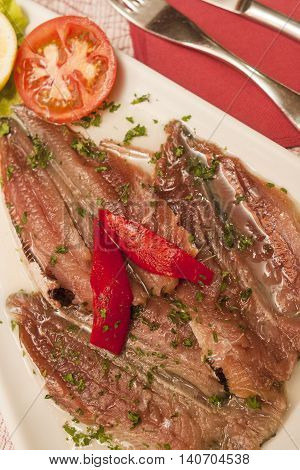 marinaded sprat with vegetables tomatoes and lemon