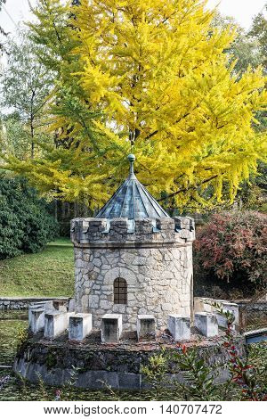 Turret in Bojnice Slovak republic. Autumn park lake and colorful trees. Seasonal park scene. Vertical composition.