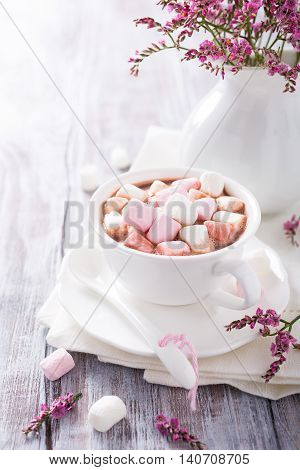 Cup of hot chocolate with mini marshmallows with pink flowers in jug on white wooden background with copy space.