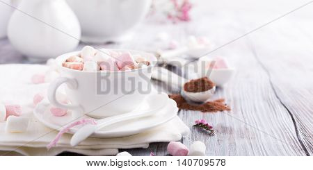 Hot chocolate with mini marshmallows with cocoa on white wooden background with copy space.
