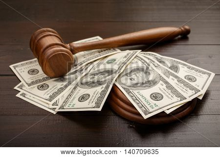 Judge gavel with dollars on brown lacquered wooden table close up with copy space. Concept for auction bidding
