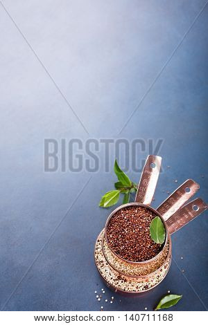 Stack of three copper measuring cups with mixed raw quinoa, South American grain, with bay laurel leaves on blue background. Healthy and gluten free food. Copy space.