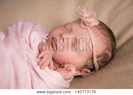 Newborn baby sleeps under a knitted pink cape. Close-up