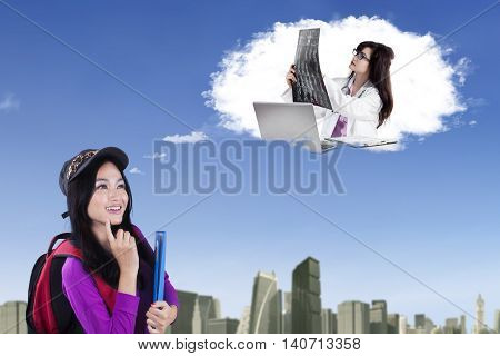 Beautiful female high school student dreaming as a doctor while looking at speech bubble