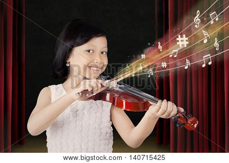 Photo of a little schoolgirl playing a violin while smiling at the camera
