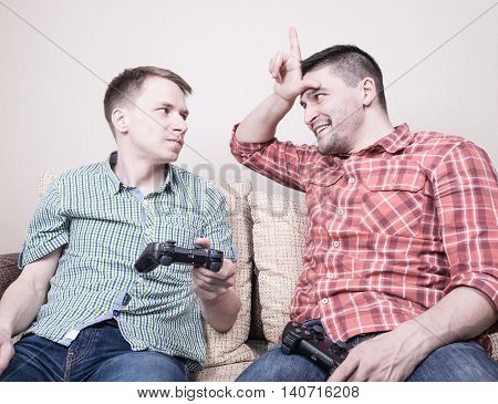 Two young guys playing video games at home holding controllers and sitting on sofa