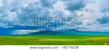 The hard rainy clouds cover the Mount Aragats surrounded by agricultural lands Armenia.