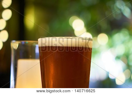 Glass of beer with beatiful ambience light