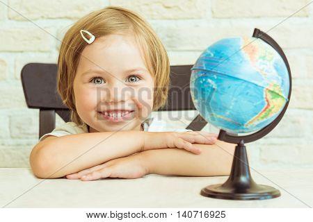 Smiling girl sitting near the globe. She folded her hands