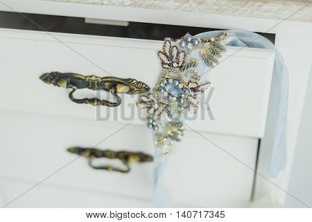 Bride's belt with rhinestones on a luxurious blue wedding dress on bedside table