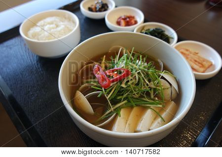 Korean clams soup with tofu and onion on wooden tray with rice