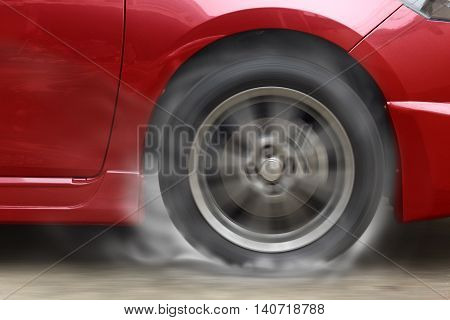 Red car racing spinning wheel burns rubber on floor.
