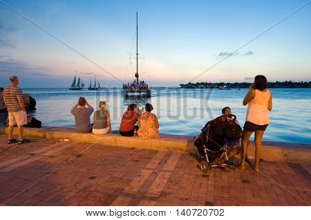 KEY WEST FLORIDA USA - MAY 03 2016: Tourists are relaxing at the waterside in the twilight on Mallory Square in Key West in Florida.