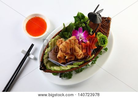 Vietnamese fried spring rolls on bamboo tray with sliced cucumber salad and chili sauce