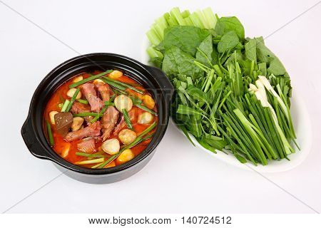 Hot pot of spicy asian duck with fermented tofu and mekong vegetables on white background