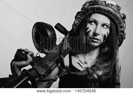 Young female soldier with ak-104 posing over white background