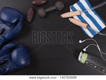 Fitness with boxing glovestoweldumbbell equipment and a bottle water. Top View from above on wooden background.