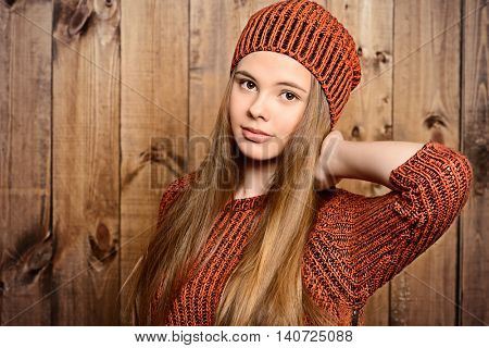 Trendy girl teenager in knitted sweater and hat stands by a wooden wall. Modern teen generation. Youth fashion. Healthy hair, haircare.