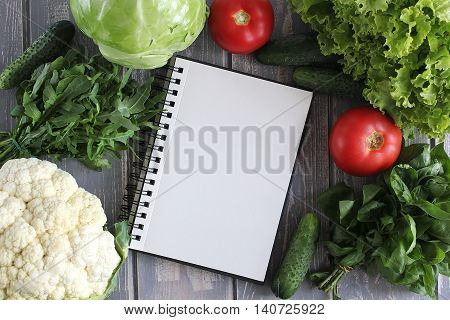 Note book and composition of vegetables on grey wooden desk. Tomato, basil, cucumber, arugula, lettuce, cauliflower. Top view. Modern photography. The best for recipies.