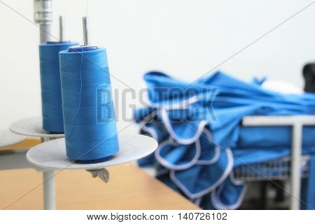 The coils of thread and clothing samples in the background