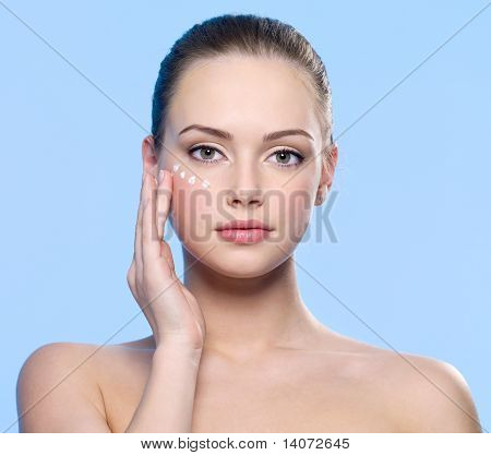 Girl Applying Cream On Her  Skin Around Eyes
