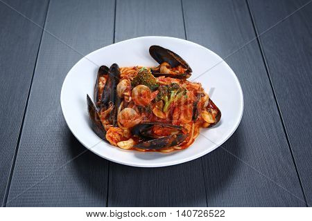 Seafood Tomato Pasta with shrimp and clams on white plate