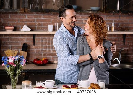 You are my queen. Contented mature man hugging an energetic woman while being in the kitchen