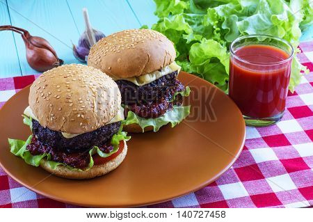 Delicious two burgers with beef tomato cheese and lettuce. Homemade hamburgers with fresh vegetables and a glass of tomato juice
