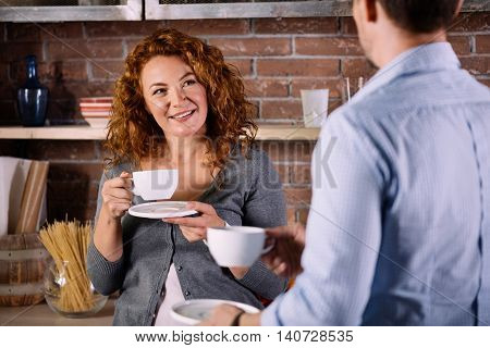 Are you sure. Curious middle aged woman looking with interested at her husband while drinking coffee at home