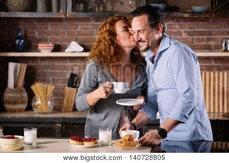 Love is in the air. Charming woman kissing her husband in chick while having breakfast with him