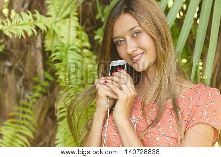 a young girl listening to music with white phone while in a summer forest