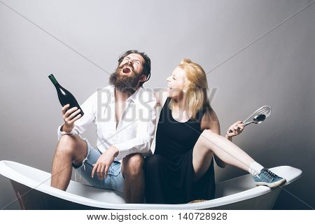 young family couple of blonde smiling pretty girl with kitchen utensils and bearded man with long beard holding wine bottle sitting on bathtub. household everyday life and routine