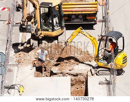 Udine ,Italy - June 28 2016 : Men at work with excavator to do the excavation for the laying of drains of a sewer.