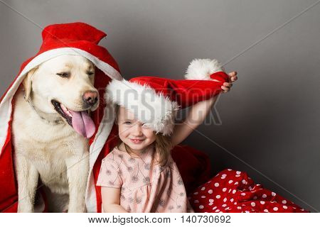 Happy little girl with smiling funny face near labrador dog pet in santa claus hat and coat in studio on grey background