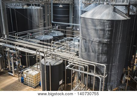 Row of stainless tanks in microbrewery. Modern interior.