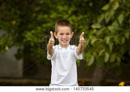 happy little boy giving thumbs up outdoors