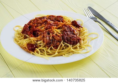 Spaghetti with tomato sauce on a yellow wooden background. Pasta with sun-dried tomatoes.