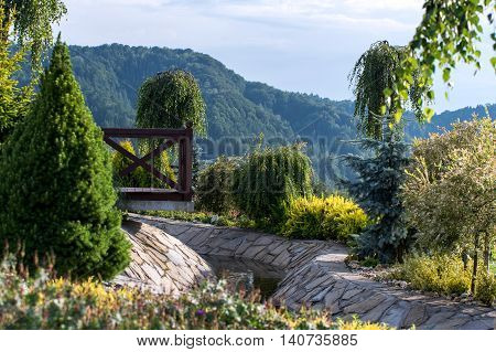 Picturesquely located on a hillside garden with a stream and a bridge