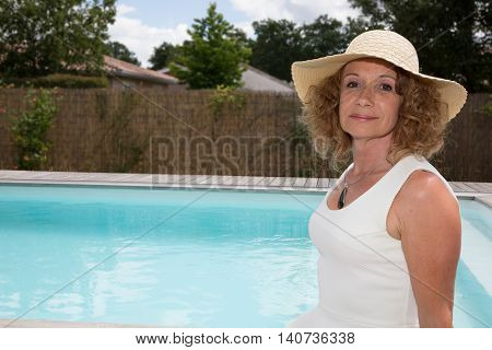 Middle Aged Sexy Woman In The Pool With A Hat And White Dress