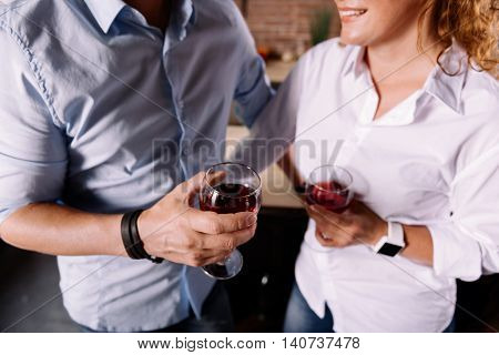Hey you relax. Close up of hands of man and a woman holding glasses with wine while standing in the kitchen
