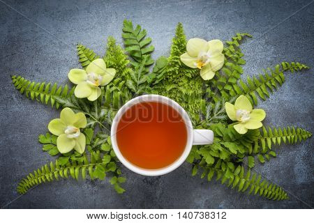 Cup of tea with fern leaf and orchid on rustic stone  background
