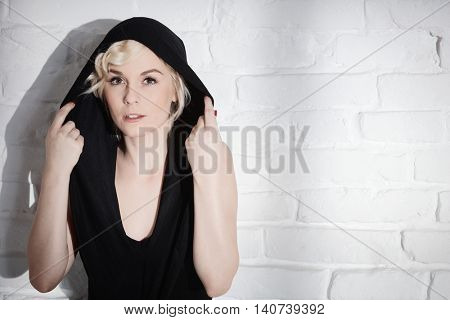 Young woman wearing hoody standing over white brick wall.
