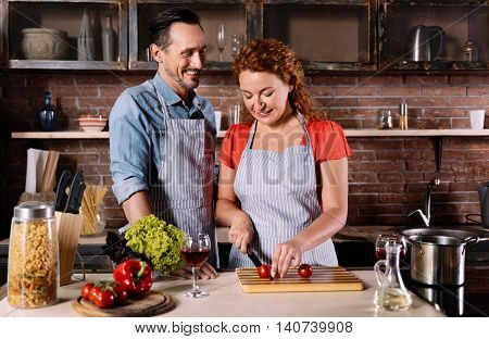 Lets make something delicious. Contented mature man and energetic woman cutting vegetables for making a dinner