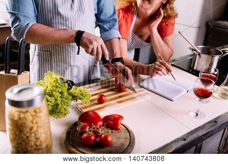 Cooking is funny. Close up of hands of a woman checking the recipe in the notebook and hands of a man cutting vegetables
