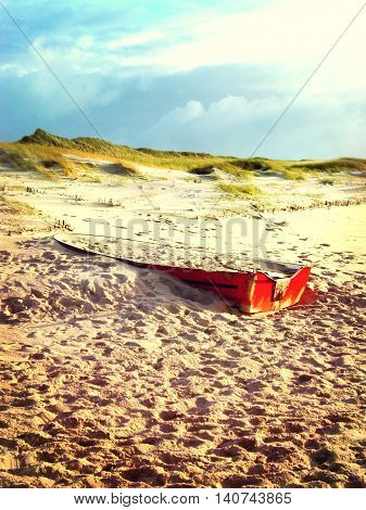 Old, red boat or sailboat on a beach.